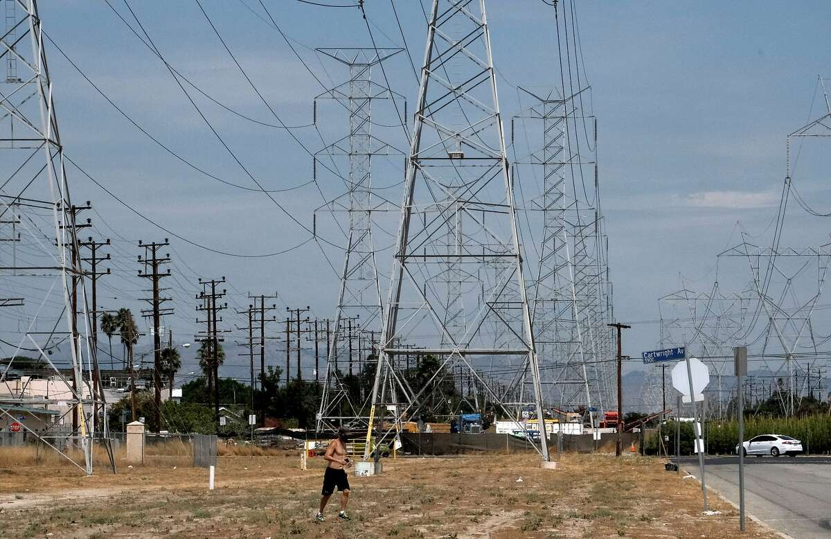 A jogger runs in extreme heat under high tension electrical lines in the North Hollywood section of Los Angeles on Saturday, Aug. 15, 2020. California has ordered rolling power outages for the first time since 2001 as a statewide heat wave strained its electrical system. (AP Photo/Richard Vogel)