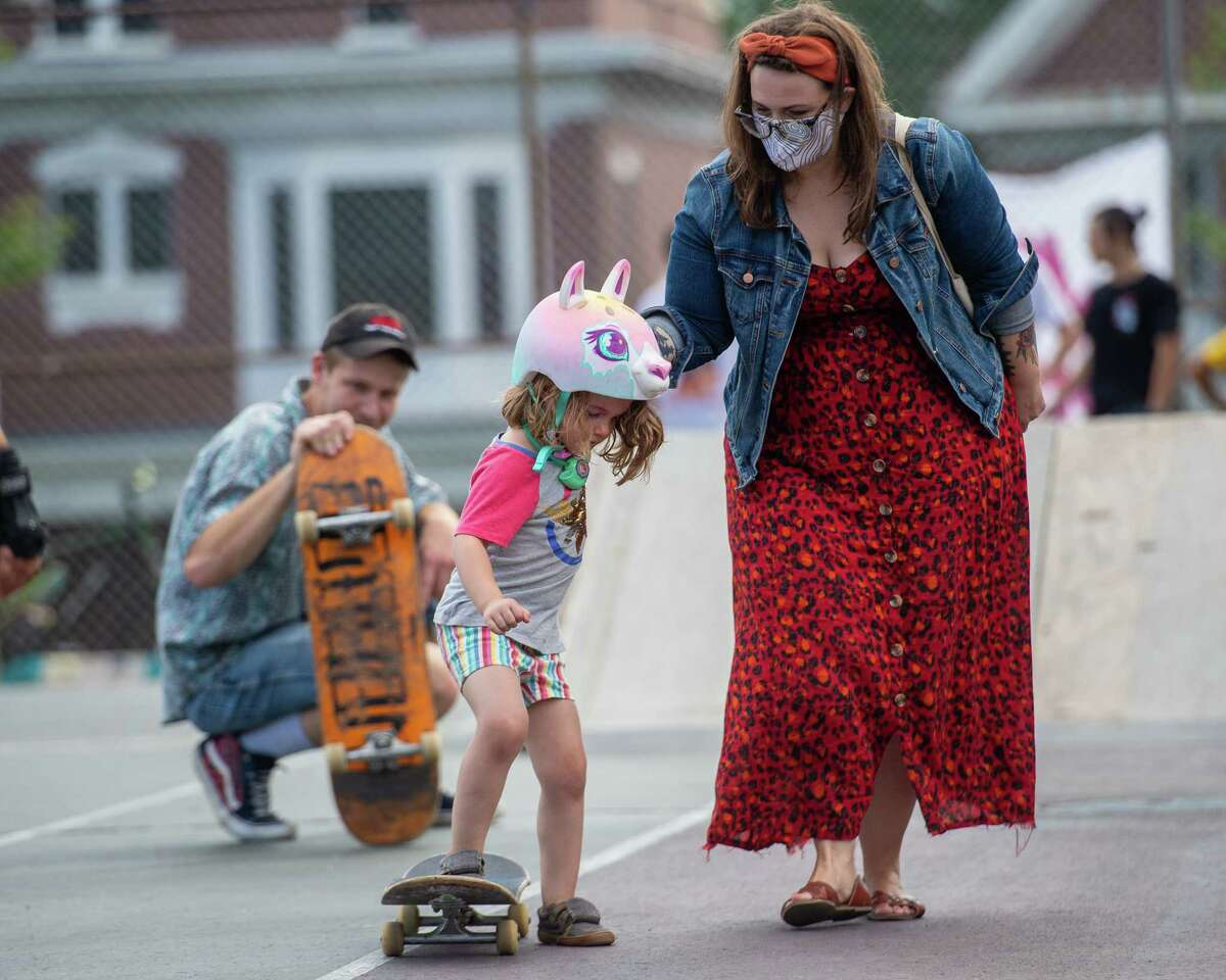 Brendon Benack, of Noteworthy Resources, watches Mary Rees help Hazel Rees get on a skateboard during an event hosted by NWR to introduce women, youth, members of the LGBTQ+ community and their allies to the sport of skateboarding at the Albany Skate Park in Washington Park in Albany, NY, on Saturday, Aug. 15, 2020 (Jim Franco/special to the Times Union.)