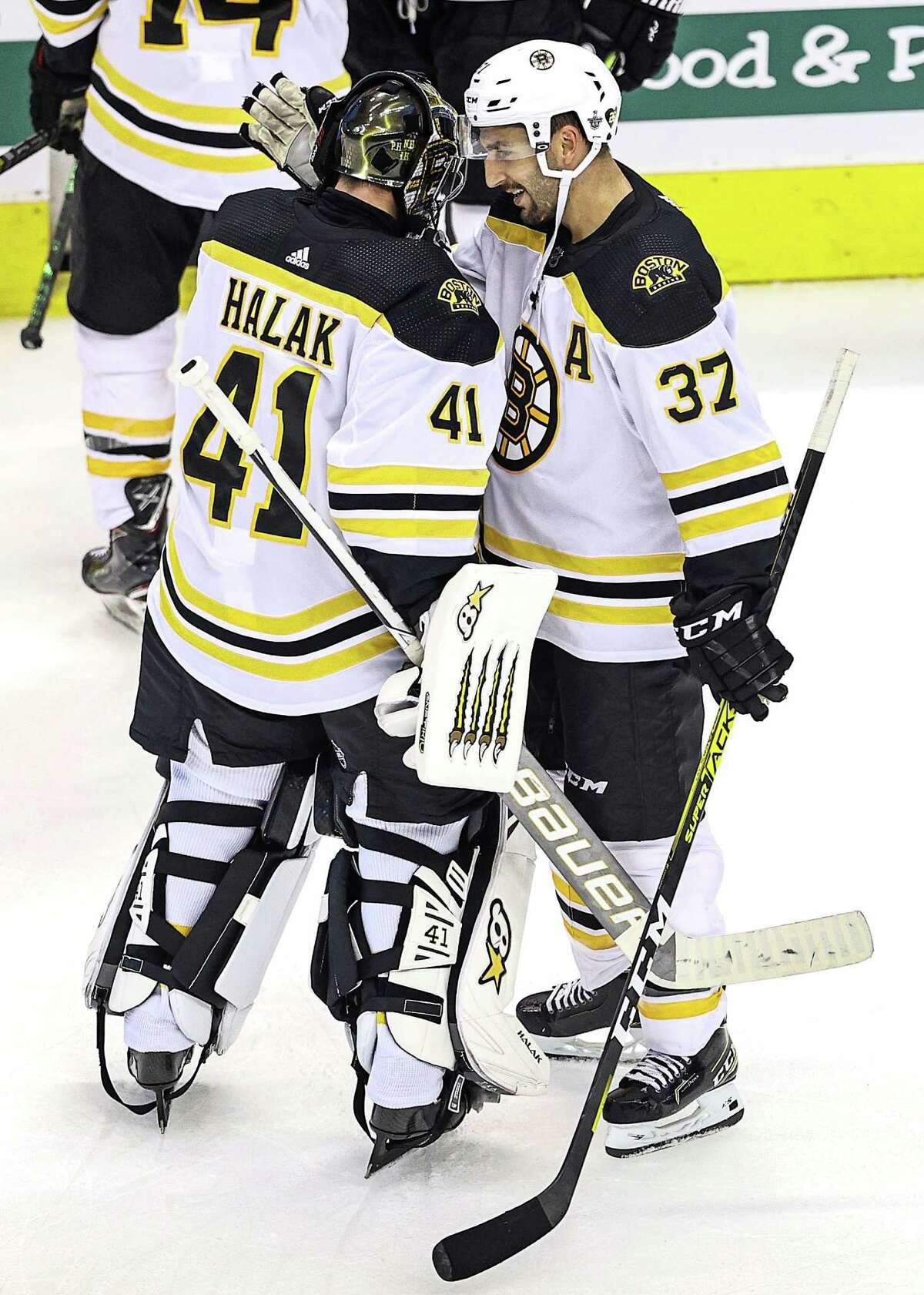 TORONTO, ONTARIO - AUGUST 15: Jaroslav Halak #41 and Patrice Bergeron #37 of the Boston Bruins celebrate their teams 3-1 win against the Carolina Hurricanes in Game Three of the Eastern Conference First Round during the 2020 NHL Stanley Cup Playoffs at Scotiabank Arena on August 15, 2020 in Toronto, Ontario. (Photo by Elsa/Getty Images)