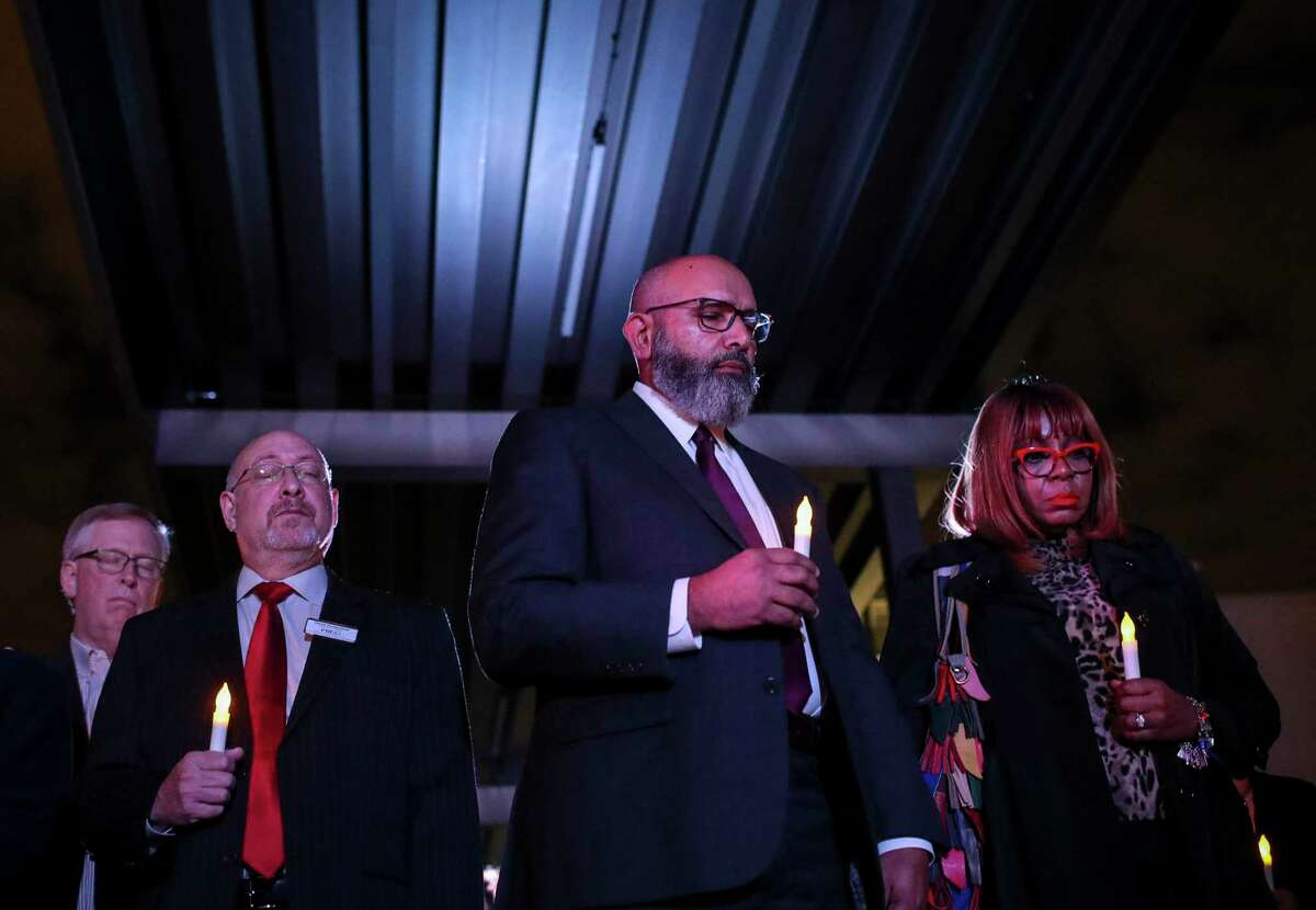 Fort Bend Independent School District Superintendent Charles Dupre, center, and others take part in a candlelight vigil to honor 95 African-Americans whose remains were found at a Sugar Land construction site, at the James Reese Career and Technical Center on Sunday, Nov. 17, 2019, in Sugar Land. The Fort Bend ISD in September 2020 released a report with information on 72 of those whom they believe to be buried on the site.