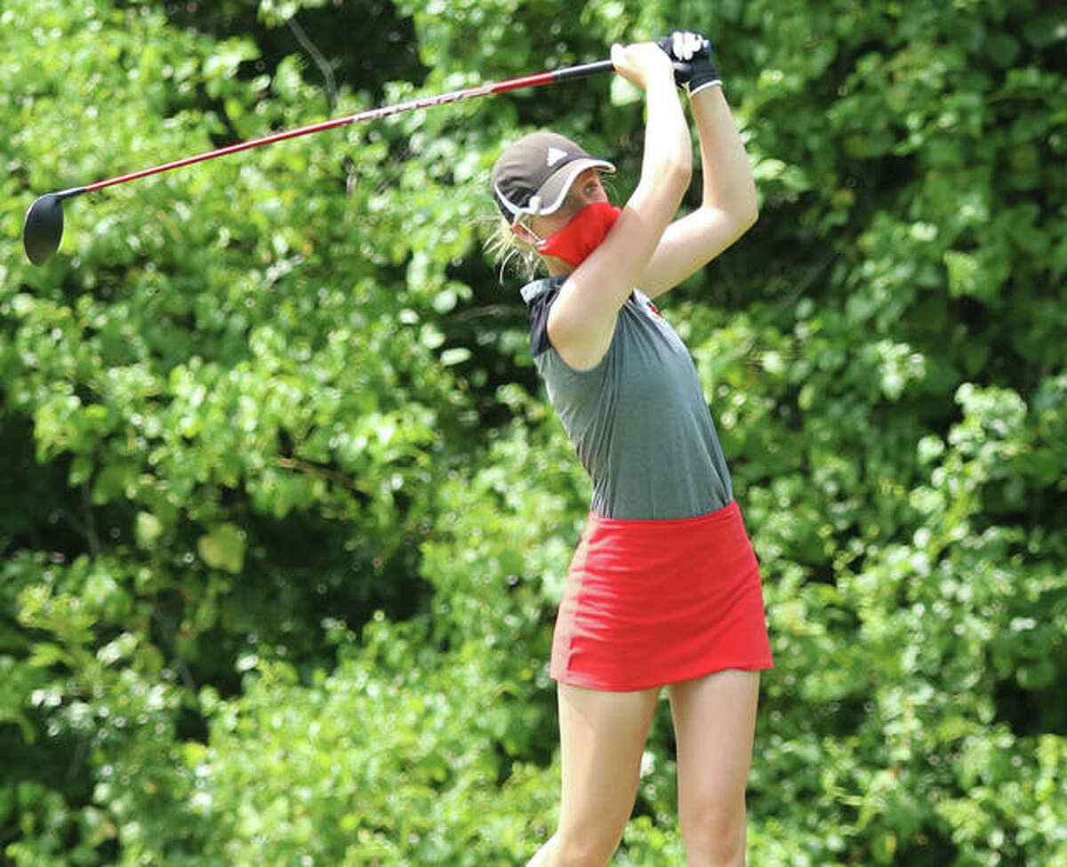Alton senior Natalie Messinger watches her drive Saturday afternoon at Rolling Hills golf course during the Redbirds Kick-Off Scramble/Shamble in Godfrey. Players are allowed to remove their masks when striking the ball, but Messinger opted to go mask-up for her tee shot. Edwardsville and O'Fallon tied for first place in the Scramble/Shamble with a 234. Belleville East was third at 234, followed by host Alton at 242, Collinsville at 249 and Highland at 283. Edwardsville's Nicole Johnson and Grace Daech won the two-player format with a 64, with Tigers teammates Riley Lewis and Caitlyn Dicks one-shot back in second at 65. Messinger and her Redbirds partner Riley Kenney came in at 1-under par 70.