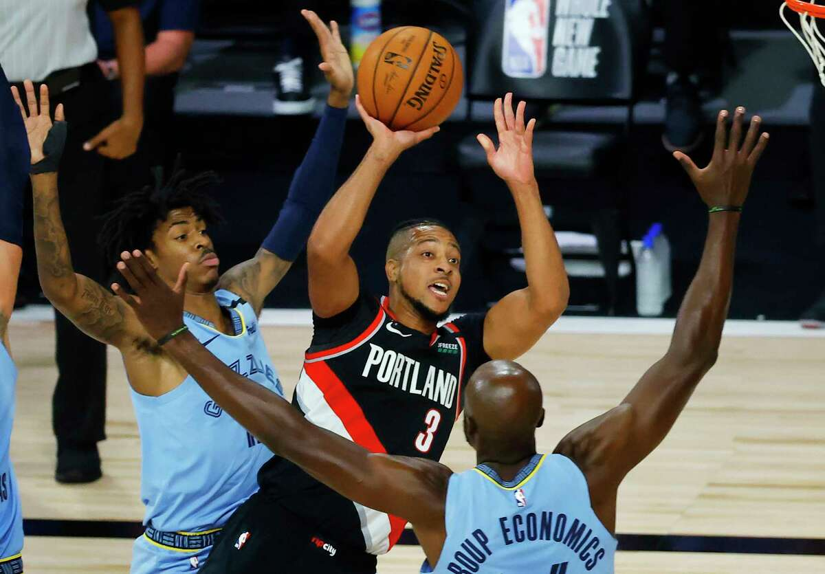 Portland Trail Blazers': CJ McCollum (3) shoots against the Memphis Grizzlies during the first half of an NBA basketball game Saturday, Aug. 15, 2020, in Lake Buena Vista, Fla. (Kevin C. Cox/Pool Photo via AP)