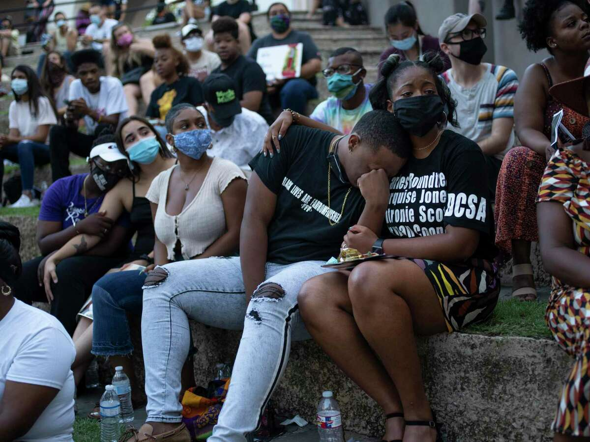 Antronie Scott Jr. center, cries during a memorial for his late father while his friend Camille Wright, right, supports him during an event put on to honor the families of victims of police violence in San Antonio, Tx., US, on Saturday, August 15, 2020. The event, ?'Healing Home,?