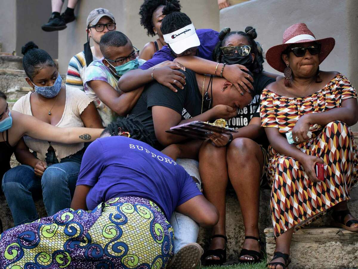 Antronie Scott Jr. center, cries during a memorial for his late father while his friends and family support him during an event put on to honor the families of victims of police violence in San Antonio, Tx., US, on Saturday, August 15, 2020. The event, ?'Healing Home,?