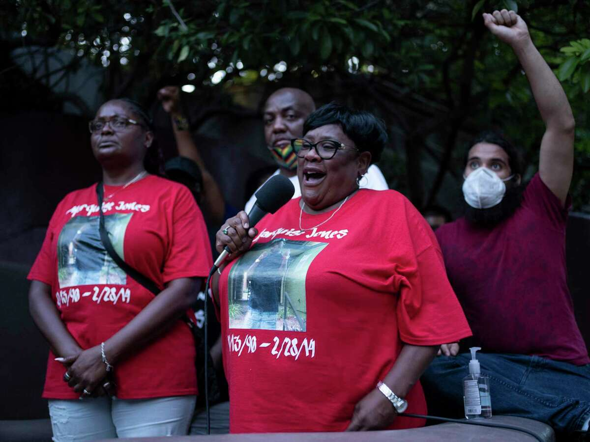 Debbie Bush, center, aunt of the late Marquise Jones, standing in front of his mother Cheryl Jones, and father Blake Lamkin, speaks about Marquise during an event to honor the families of victims of police violence in San Antonio on August 15, 2020.