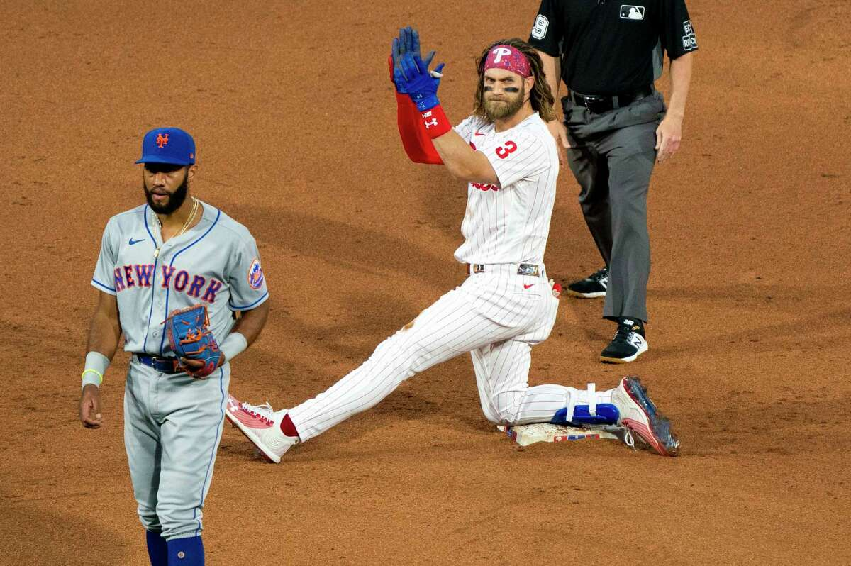Philadelphia Phillies' Bryce Harper, right, reacts to his RBI double with New York Mets shortstop Amed Rosario, left, looking on during the fifth inning of a baseball game, Saturday, Aug. 15, 2020, in Philadelphia. The Phillies won 6-2. (AP Photo/Chris Szagola)