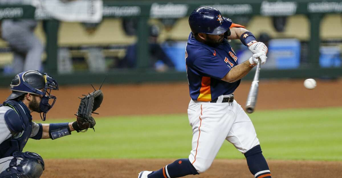 Houston Astros second baseman Jose Altuve (27) hits a single against the Seattle Mariners during the seventh inning of an MLB game at Minute Maid Park on Saturday, Aug. 15, 2020, in Houston.