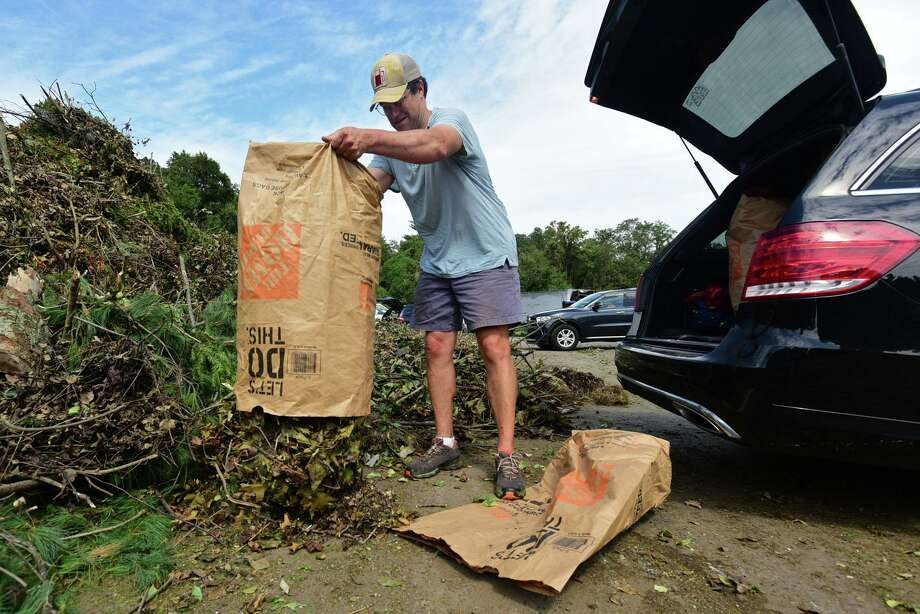 Greenwich residents including Andrew Hertzmark dump their lawn refuse at the Holly Hill Transfer Station Saturday, August 15, 2020, in Greenwich, Conn. In order to help accommodate the quantity of organics debris coming into the Holly Hill Transfer Station as a result of Tropical Storm Isaias, operating hours will be extended from 7a.m. to 2 p.m. both Saturday August 15 and Saturday August 22. Photo: Erik Trautmann / Hearst Connecticut Media / Norwalk Hour