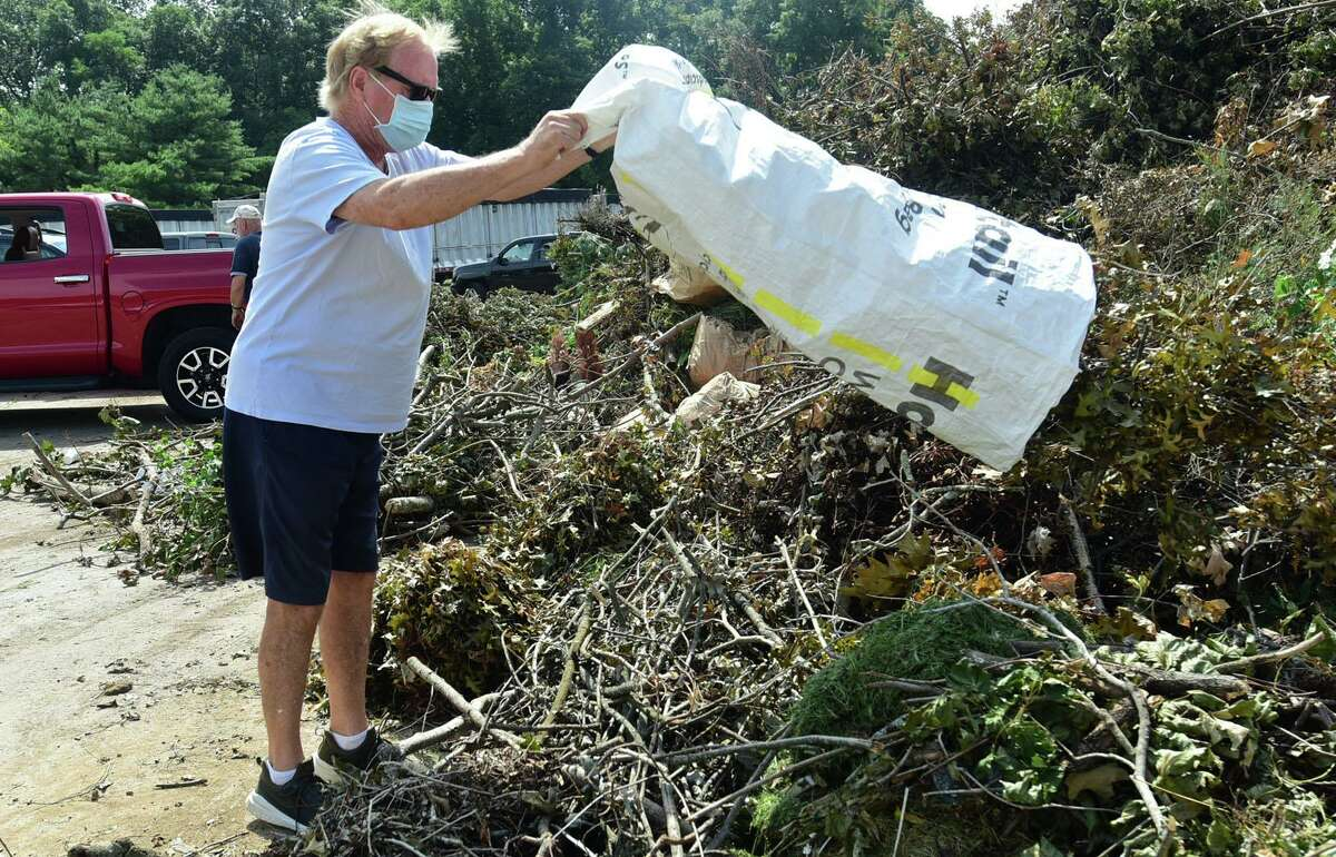 Greenwich residents including Ian Maddocks dump their lawn refuse at the Holly Hill Transfer Station Saturday, August 15, 2020, in Greenwich, Conn., as part of the cleanup after Tropical Storm Isaias.