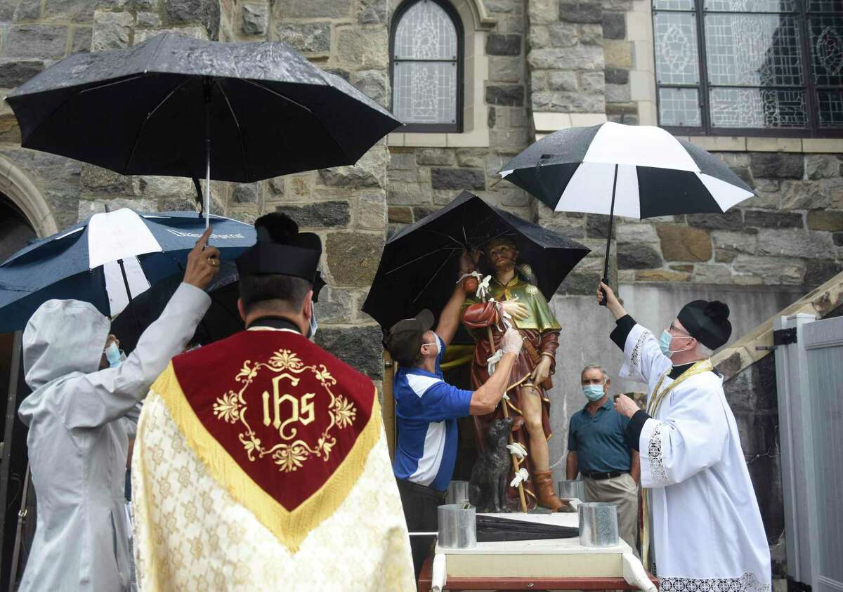 Procession organizer James Micik and the Rev. Carl D. McIntosh, far right, hold umbrellas over the statue of St. Roch at the annual St. Roch Church procession in the Chickahominy section of Greenwich, Conn. Sunday, Aug. 16, 2020. The traditional St. Roch Feast street festival and carnival was cancelled this year due to coronavirus concerns, but the procession through the streets continued in a modified fashion. Despite rain, a couple dozen congregants marched with the statue of St. Roch - coincidentally, the patron saint of infectious disease.