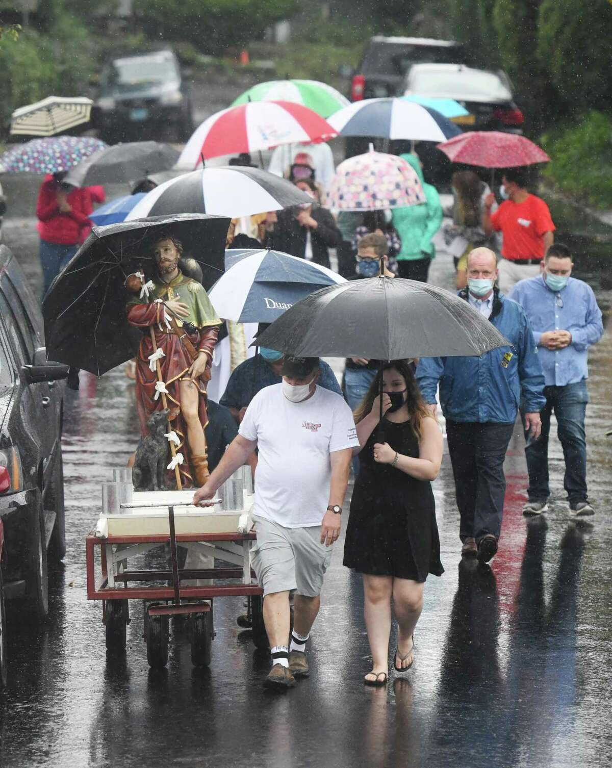 Led by Cos Cob's Carmine Raiente and his daughter, Kaitlyn Raiente, 13, the statue of St. Roch is wheeled through the street during the annual St. Roch Church procession in the Chickahominy section of Greenwich, Conn. Sunday, Aug. 16, 2020. The traditional St. Roch Feast street festival and carnival was cancelled this year due to coronavirus concerns, but the procession through the streets continued in a modified fashion. Despite rain, a couple dozen congregants marched with the statue of St. Roch - coincidentally, the patron saint of infectious disease.
