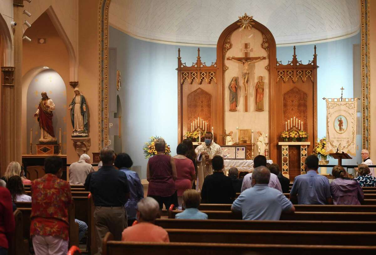 A church service in Italian is held before the annual St. Roch Church procession in the Chickahominy section of Greenwich, Conn. Sunday, Aug. 16, 2020. The traditional St. Roch Feast street festival and carnival was cancelled this year due to coronavirus concerns, but the procession through the streets continued in a modified fashion. Despite rain, a couple dozen congregants marched with the statue of St. Roch - coincidentally, the patron saint of infectious disease.
