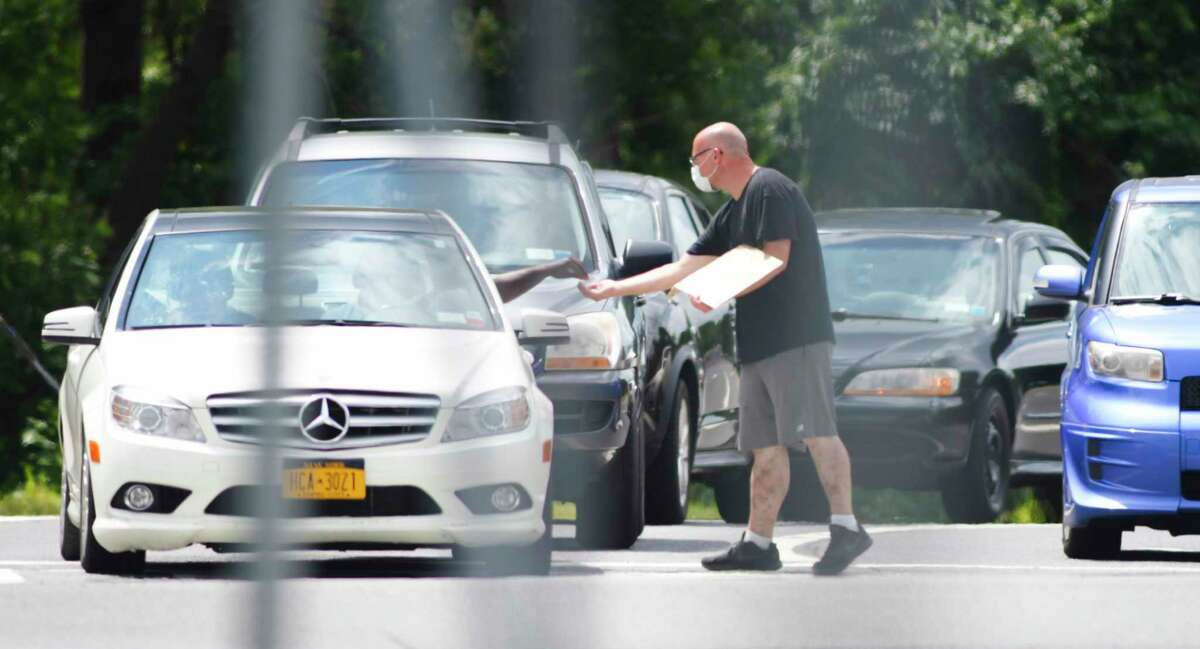A man panhandles along Central Ave. at the Wolf Road exit from Interstate 87 on Sunday, Aug. 16, 2020, in Colonie, N.Y. (Paul Buckowski/Times Union)