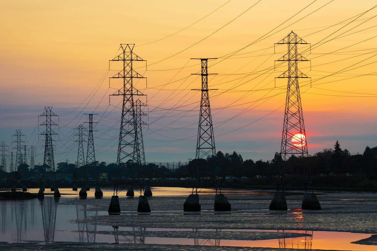 FILE - A power transmission tower is silhouetted by the rising sun in Burlingame, on Oct. 26, 2019. A record-breaking heat wave has strained California's electrical system, causing The California Independent System Operator (California ISO) to direct utilities around the state to implement rolling power outages.