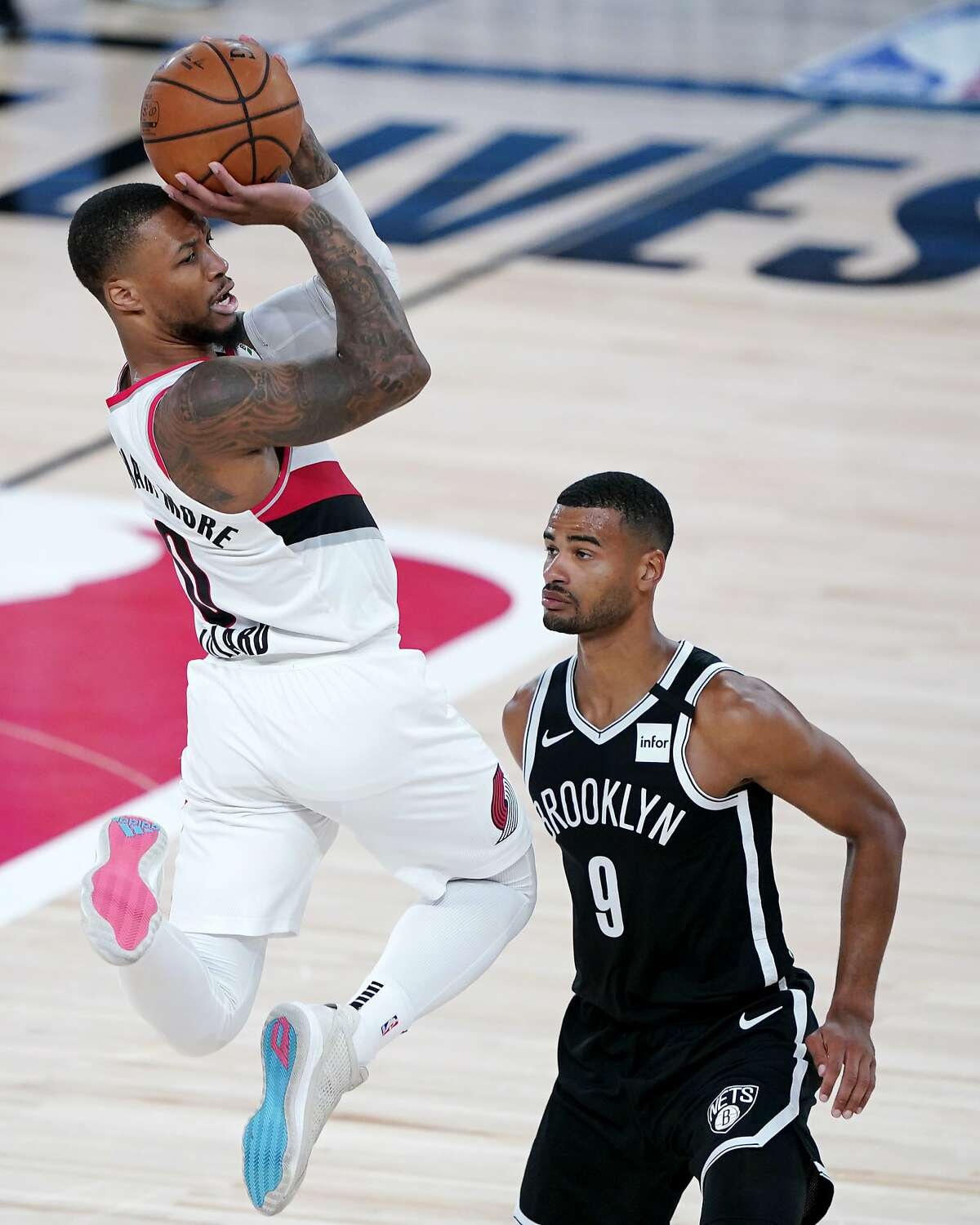 Portland Trail Blazers' Damian Lillard, left, goes up with the ball against Brooklyn Nets' Timothe Luwawu-Cabarrot during the first half of an NBA basketball game Thursday, Aug. 13, 2020 in Lake Buena Vista, Fla. (AP Photo/Ashley Landis, Pool)