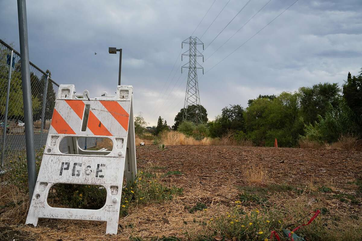 A PG&E sign is placed near power lines on Palm Avenue and Vista Way in Martinez, Calif., on Sunday, August 16, 2020. California has ordered rolling power outages for the first time since 2001 as a statewide heat wave strained its electrical system.
