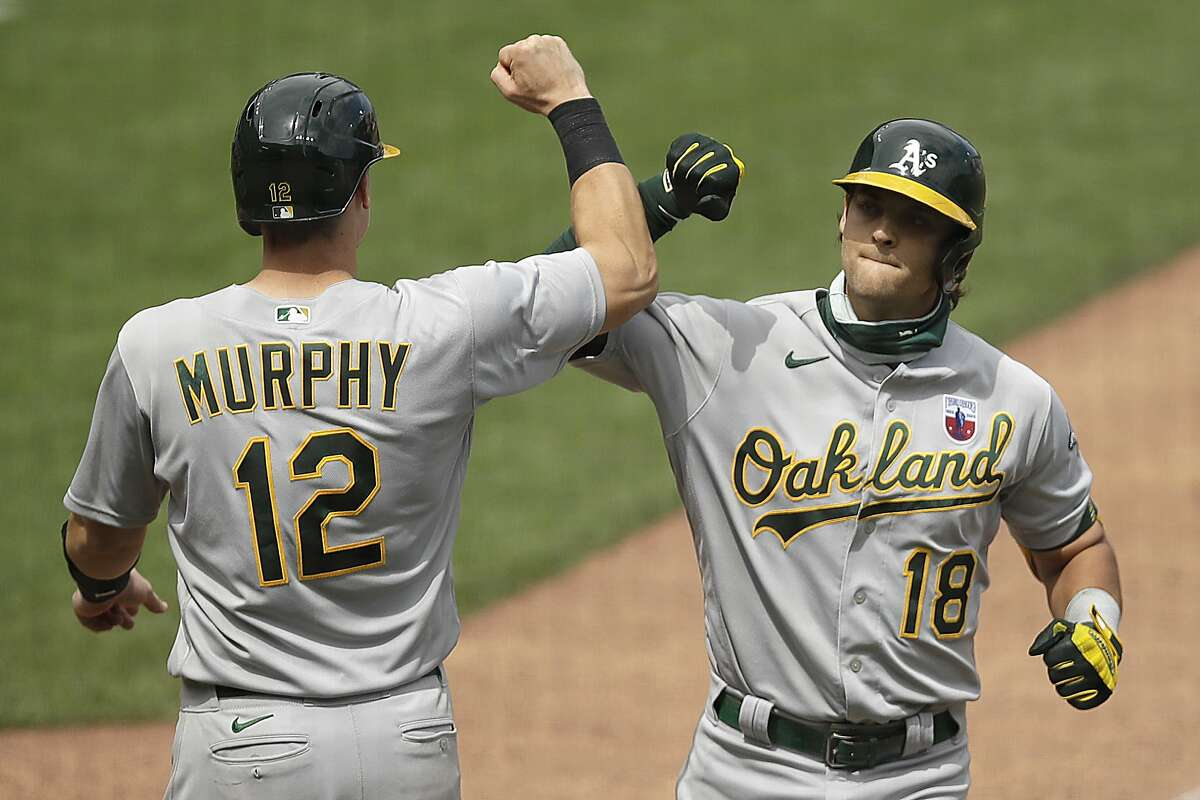 Oakland Athletics' Chad Pinder, right, celebrates with Sean Murphy (12) after hitting a two run home run off San Francisco Giants' Wandy Peralta in the fifth inning of a baseball game Sunday, Aug. 16, 2020, in San Francisco. (AP Photo/Ben Margot)
