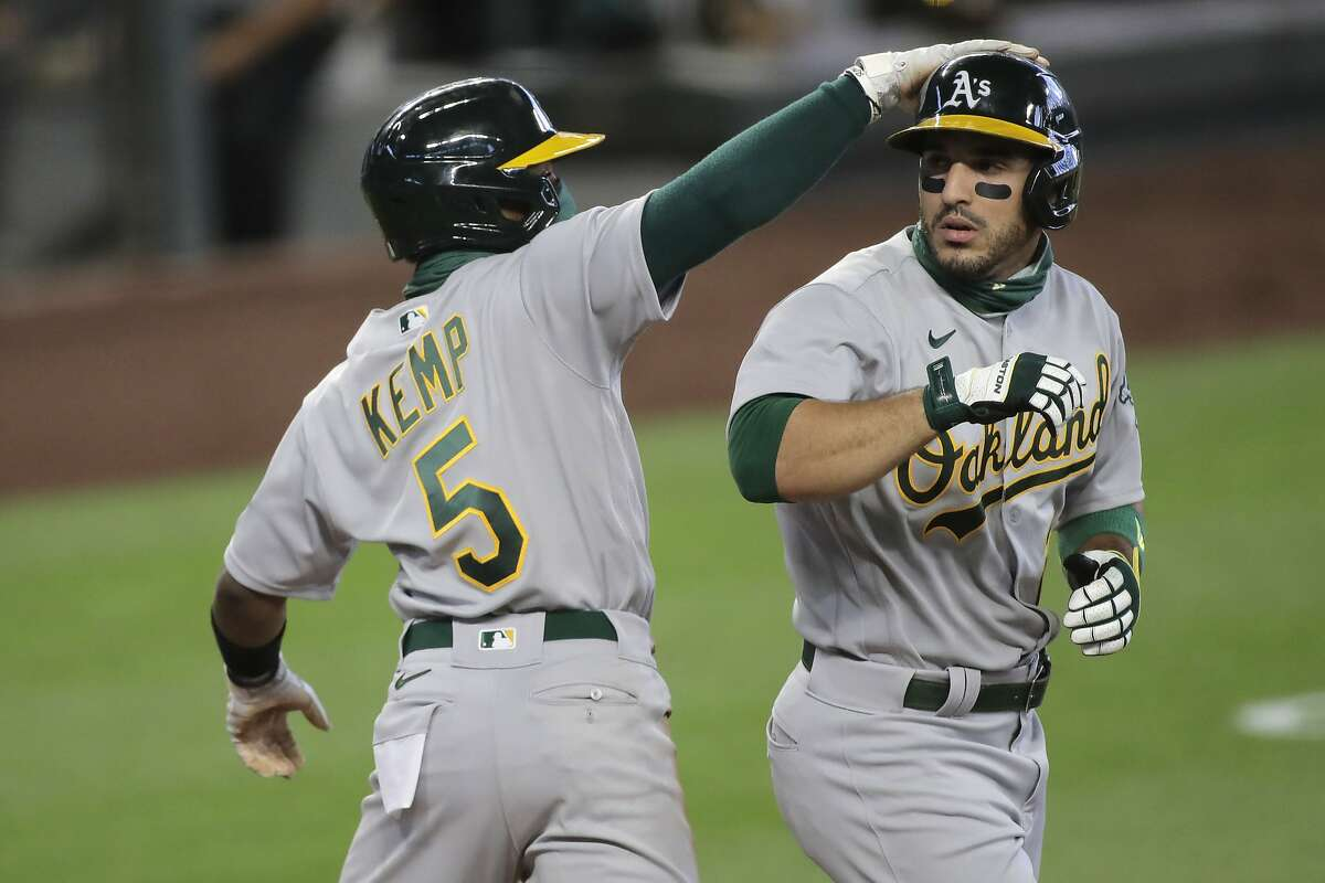 Oakland Athletics' Ramon Laureano, right, is greeted by Tony Kemp (5) after Laureano hit a three run home run to score Kemp and Marcus Semien during the fifth inning of a baseball game against the Seattle Mariners, Sunday, Aug. 2, 2020, in Seattle. The Athletics won 3-2. (AP Photo/Ted S. Warren)
