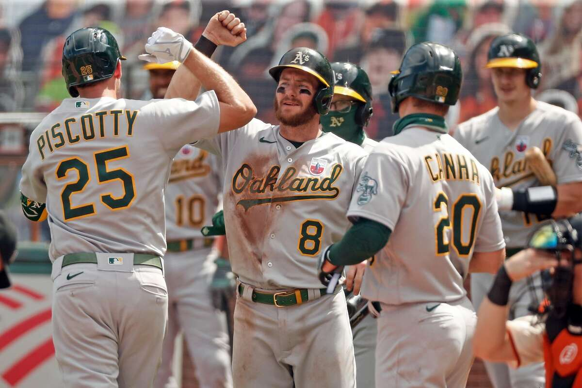 Oakland Athletics' Robbie Grossman elbow bumps Stephen Piscotty after Piscotty's 3-run home run during A's 9-run 5th inning against San Francisco Giants during MLB game at Oracle Park in San Francisco, Calif., on Sunday, August 16, 2020.
