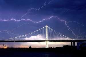 Lightning forks over the San Francisco-Oakland Bay Bridge as a storm passes over Oakland, Calif., Sunday, Aug. 16, 2020.