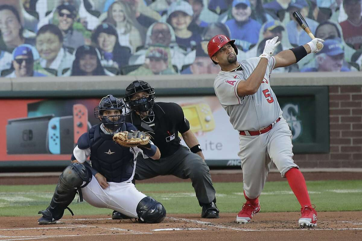 Los Angeles Angels' Albert Pujols watches his two-run home run as Seattle Mariners catcher Austin Nola looks on during the first inning of a baseball game, Tuesday, Aug. 4, 2020, in Seattle. (AP Photo/Ted S. Warren)