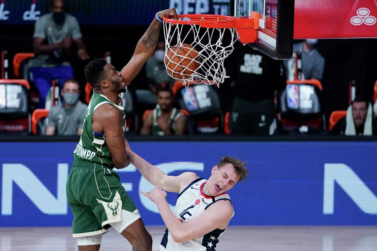 Milwaukee Bucks' Thanasis Antetokounmpo, left, slams a dunk over Washington Wizards' Anzejs Pasecniks (18) during the second half of an NBA basketball game, Tuesday, Aug. 11, 2020, in Lake Buena Vista, Fla. (AP Photo/Ashley Landis, Pool)