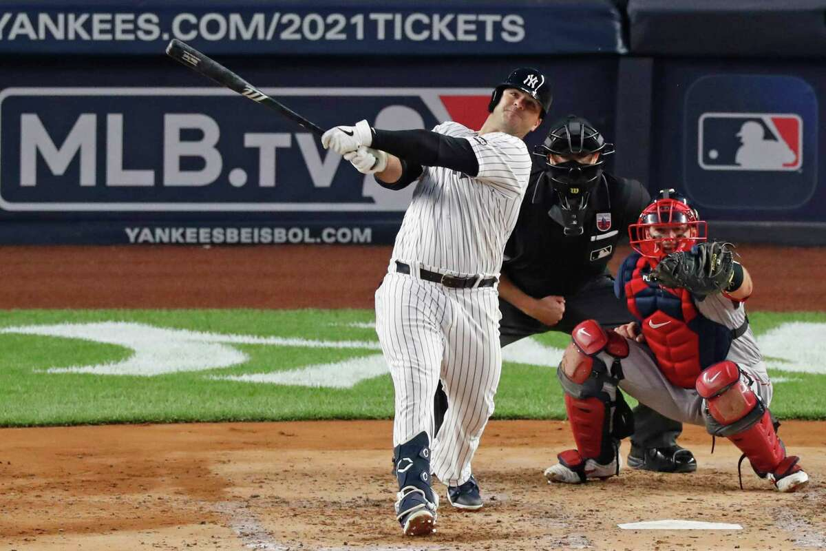 New York Yankees Mike Ford, left, follows through on a two-run home run during the third inning of a baseball game against the Boston Red Sox, Sunday, Aug. 16, 2020, in New York. Red sox catcher Kevin Plawecki, right, and home plate umpire Ryan Additon, center, watch. (AP Photo/Kathy Willens)