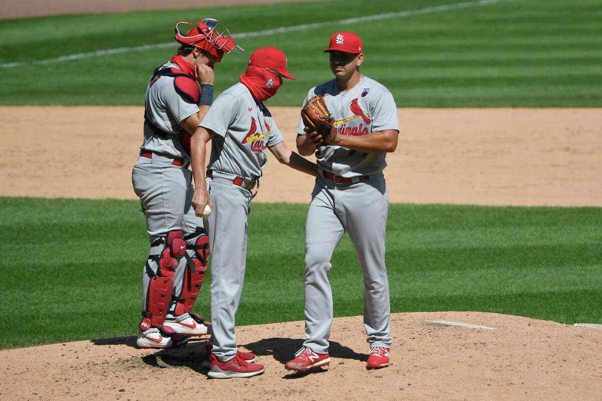 Roel Ramirez, right, hands the ball to St. Louis Cardinals manager Mike Shildt in the fifth inning on Aug. 16, 2020 in Chicago, Illinois. Ramirez was called up by the Cardinals after making 18 relief appearances this season at the Triple-A level.