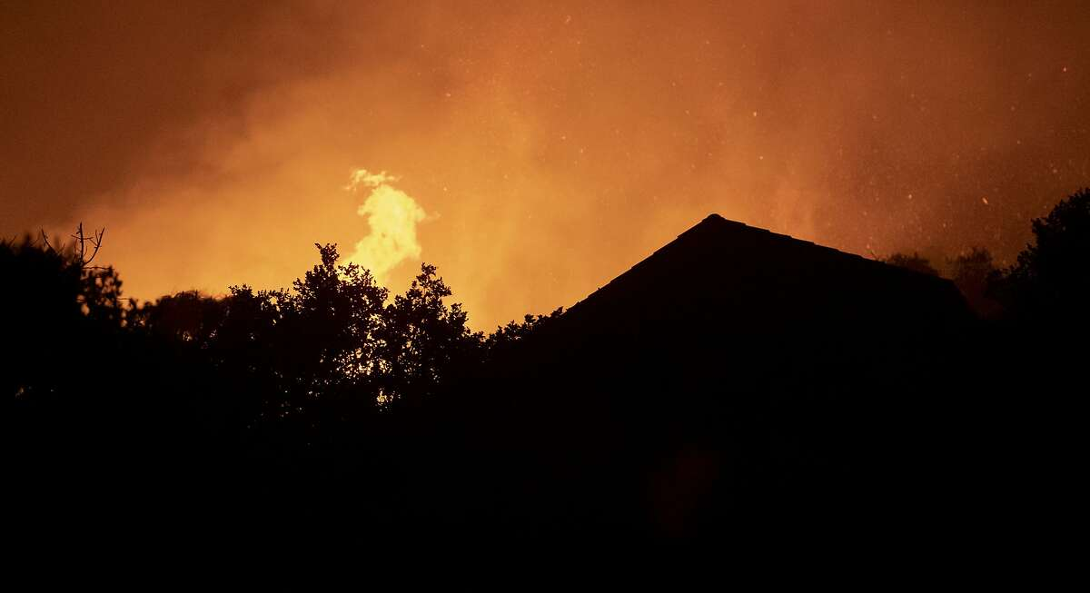 Large flames from the River Fire burn behind a home near Salinas, Calif., Sunday, Aug. 16, 2020. (AP Photo/Nic Coury)
