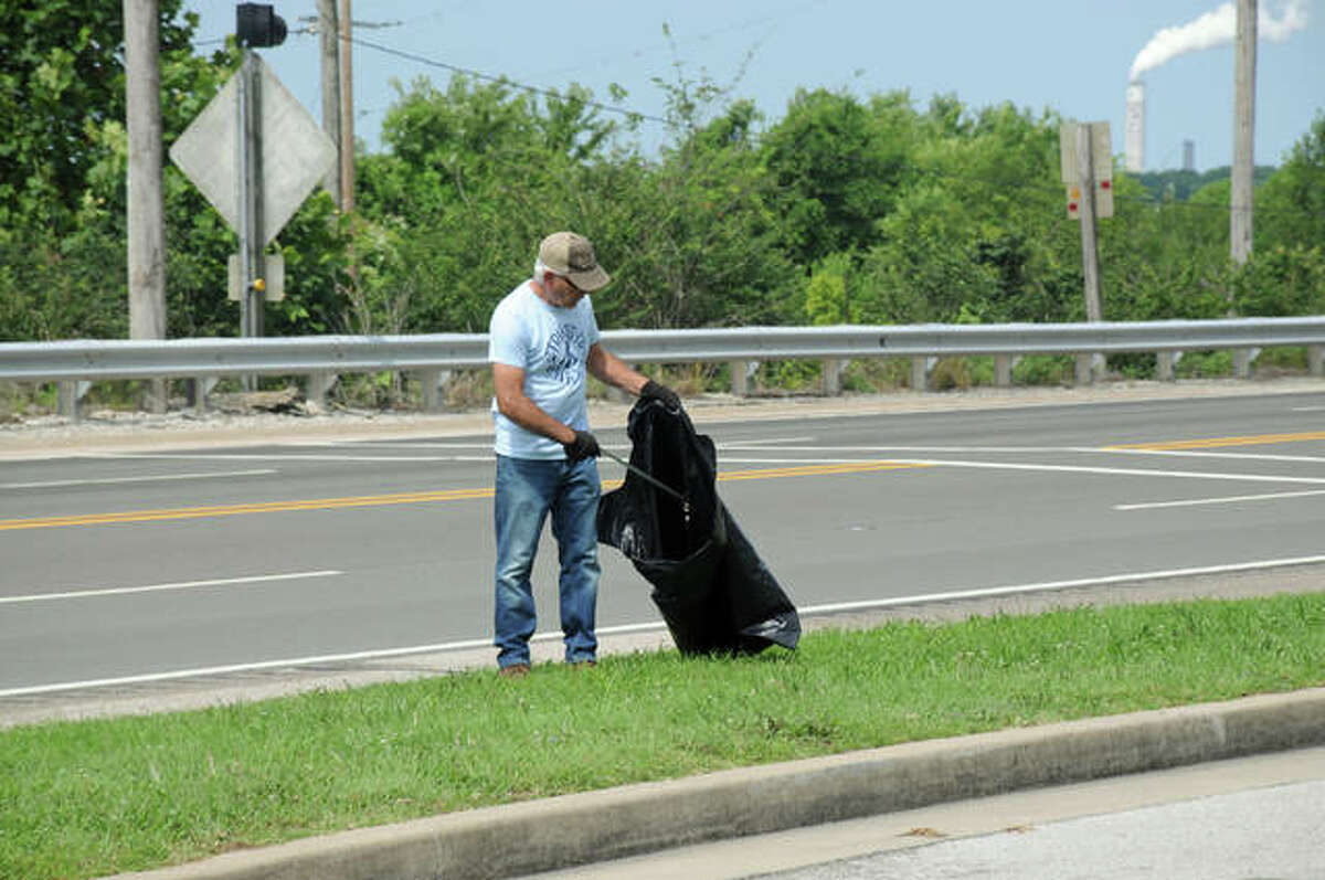 Trinity Buel's grandfather, Gary Gray, of Godfrey, picks up trash along Route 100 during the Trinity's Way cleanup Sunday.