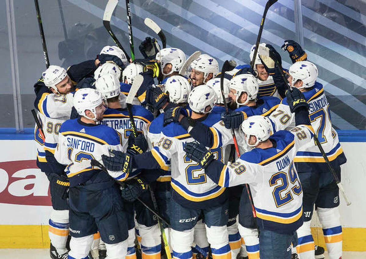 The Blues celebrate their game-winning goal in overtime to beat the Vancouver Canucks in Game 3 of a NHL first-round playoff series late Sunday night in Edmonton, Alberta. The Canucks lead the series 2-1 with Game 4 on Monday night.