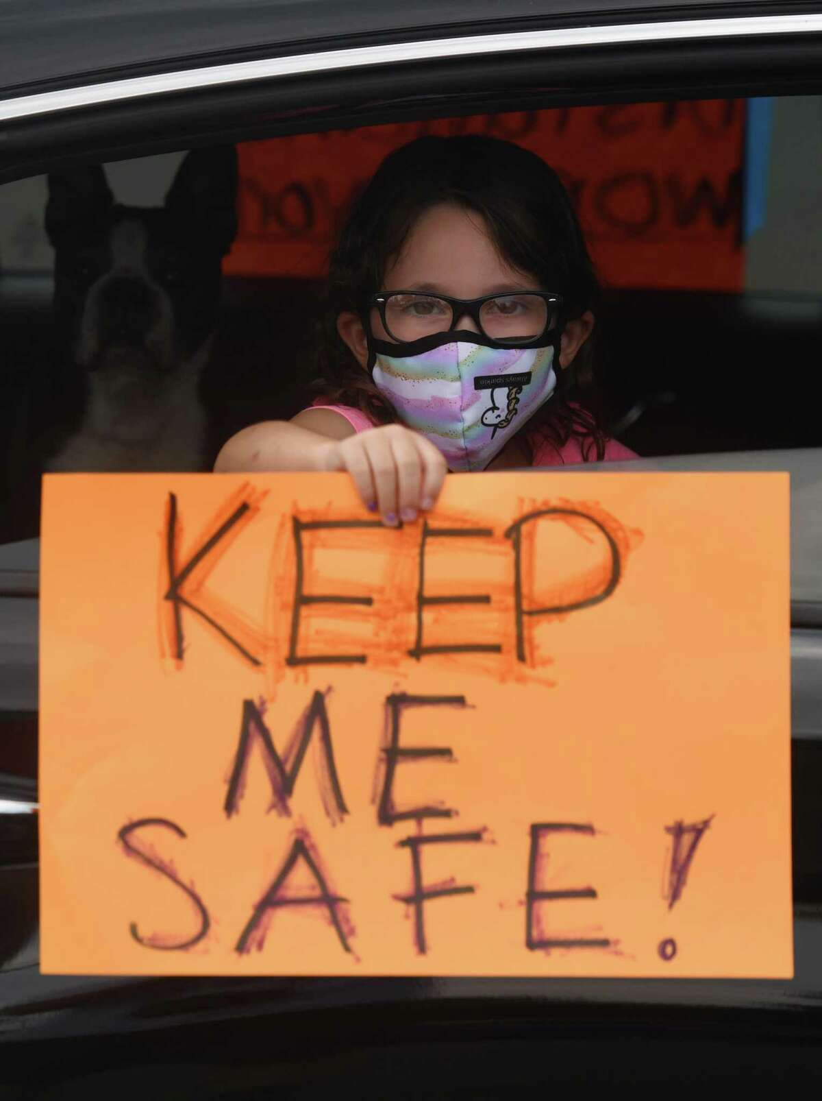 A student holds a sign in the teachers' protest caravan in the Horseneck Lane parking lot in Greenwich on July 30.