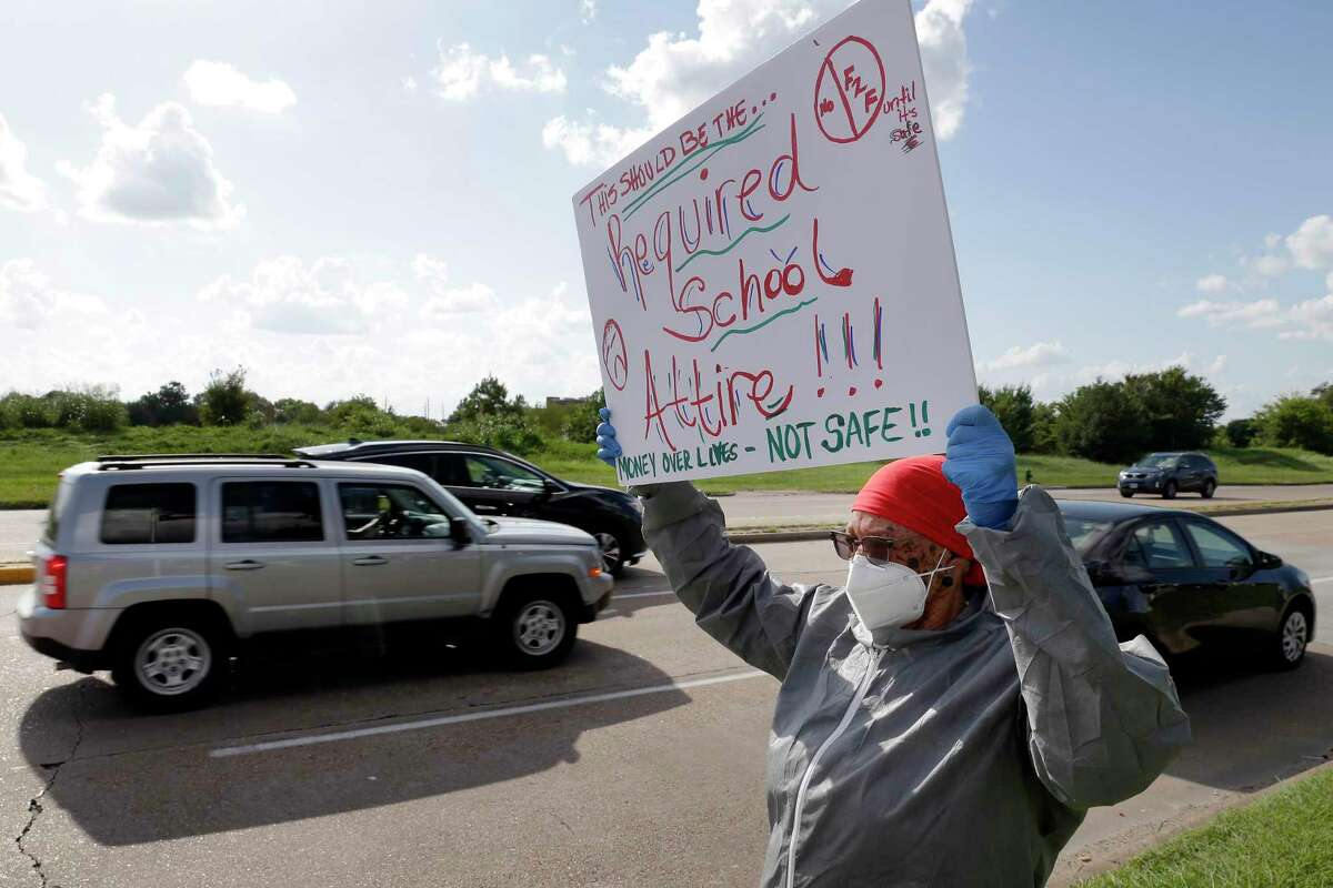 Cy-Fair teacher waves her protest sign at passing traffic at the main entrance to the district administration building against the COVID-19 teaching requirements before a Cy-Fair school board meeting Monday, Aug. 10, 2020 in Houston, TX.