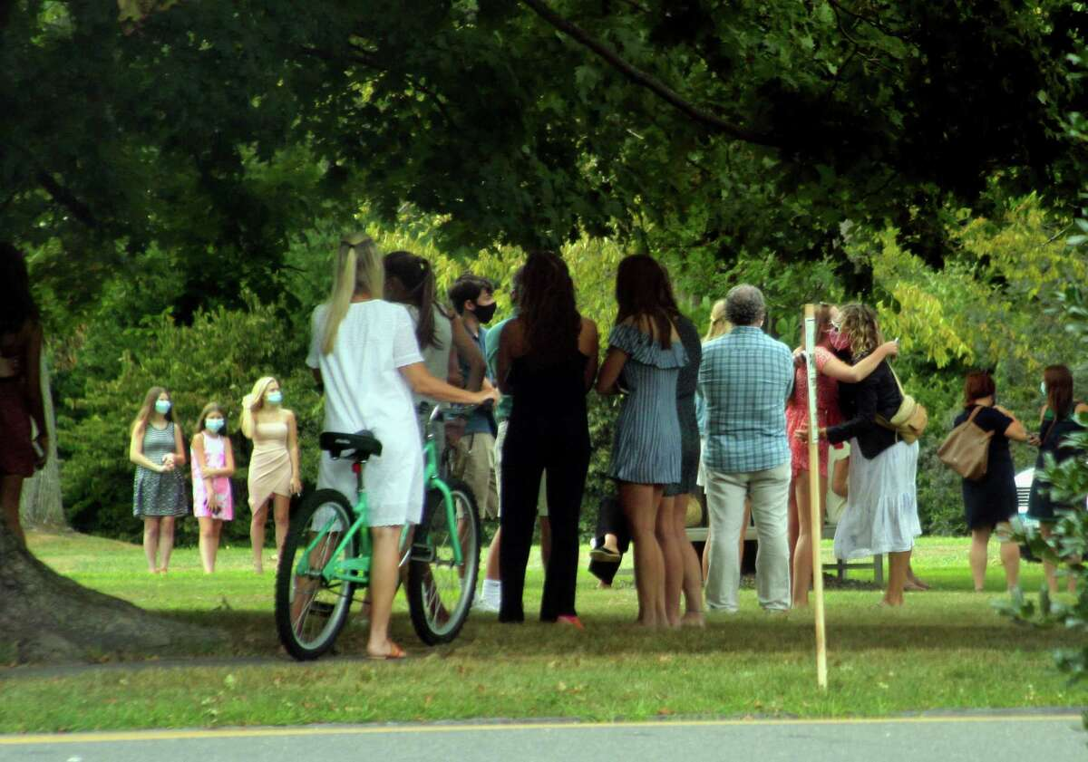 A memorial for members of the community is held for 16-year-old Southport resident Jake Panus on the lawn outside of the Pequot Library in Southport, Conn., on Saturday Aug. 15, 2020. Top right, the Panus family leave a service at Southport Congregational Church for the teen. Panus died in a car accident on Block Island Sunday.