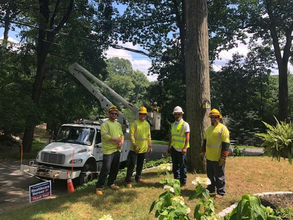 A crew from Sumter Utilities of Ashville, N.C., contracted by Eversource, restores power to a home in in Wilton on Aug. 12, 2020.