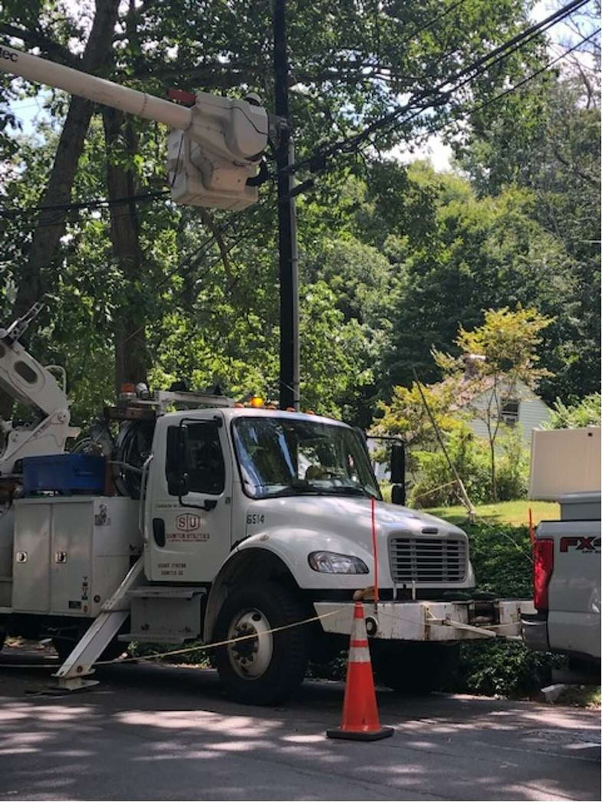 A bucket truck from Sumter Utilities repairs the faulty cables running from Wilridge Road to Adolfo Briceno's home on Wednesday in Wilton.