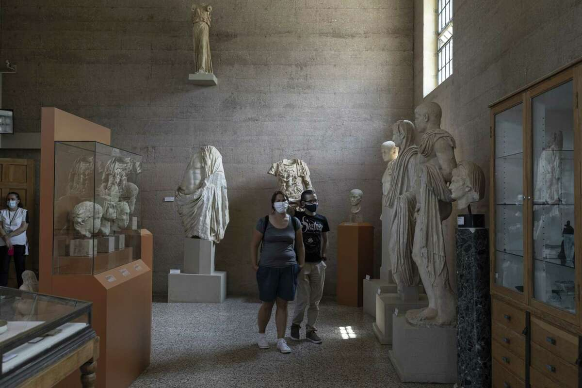 Tourists wearing protective face masks among exhibits inside the Museum of Ancient Corinth, Greece, on Aug. 1, 2020.