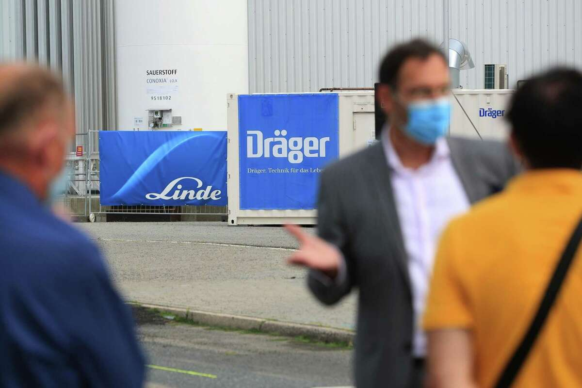 Attendees wear protective face masks near Linde and a Draegerwerk logos on banners outside the Jaffestrasse Corona Treatment Center at the Berlin Messe exhibition space in Berlin on Aug. 14, 2020.