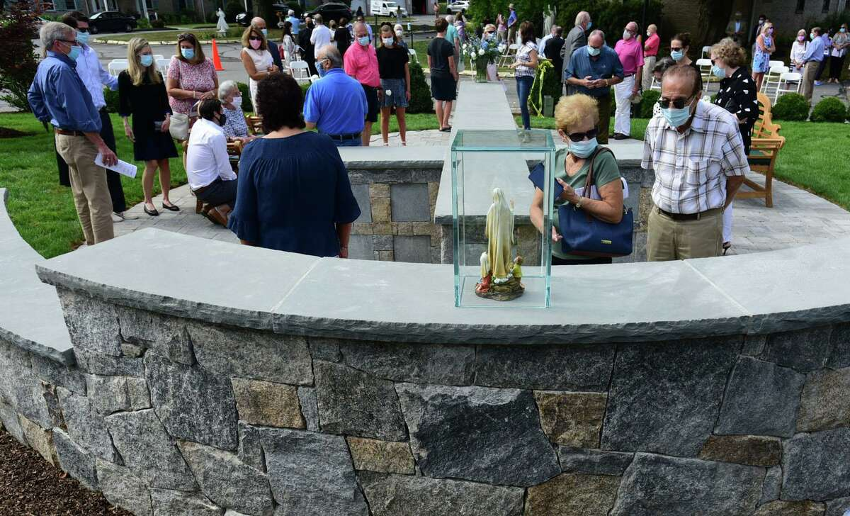 Guests attend the dedication of the Philip Tai-Lauria memorial garden at Our Lady of Fatmina Catholic Church, Saturday, August 15, 2020, in Wilton, Conn.