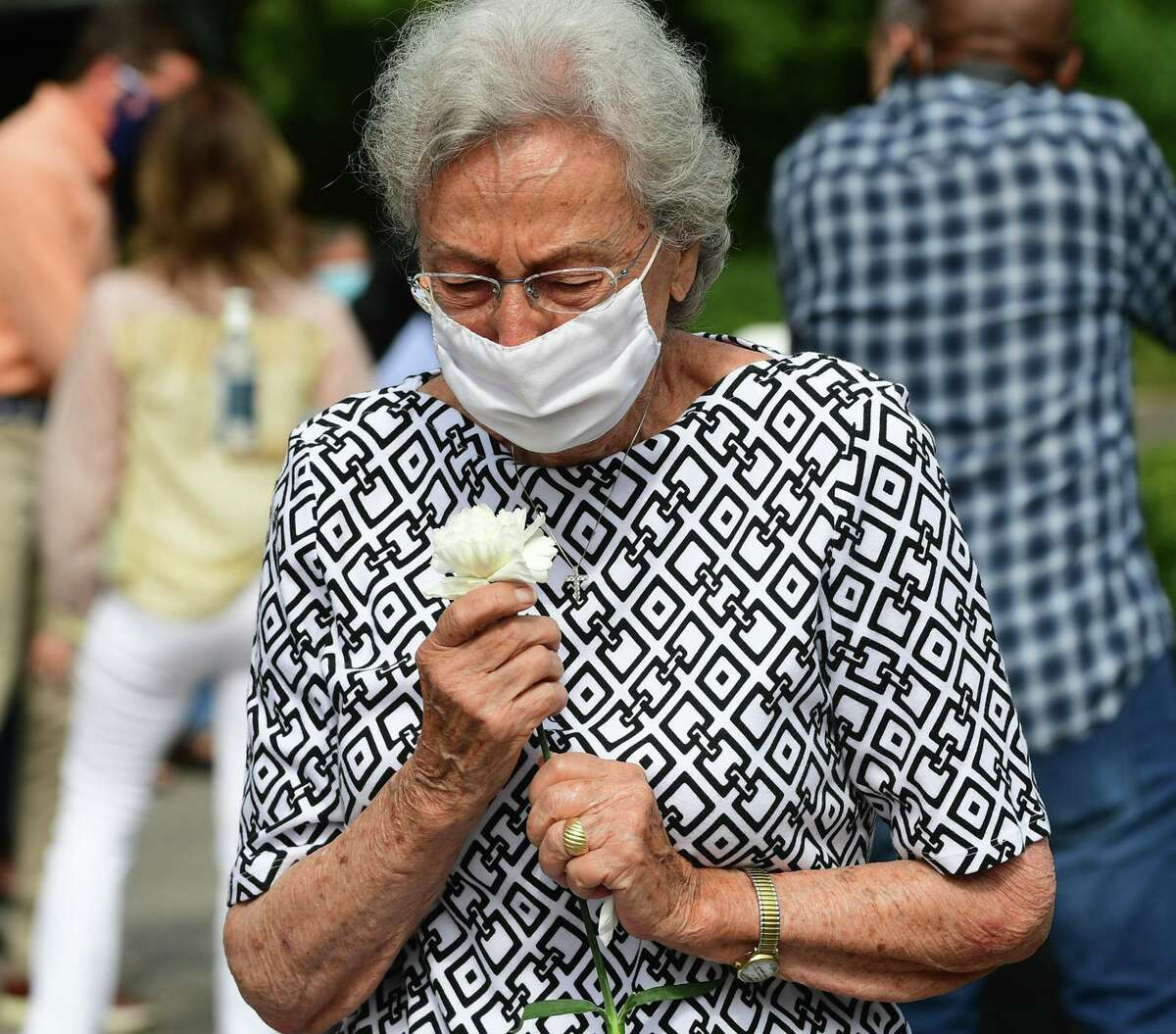 Lidia Amendola holds the white carnation she and other family members of those remembered at the Philip Tai-Lauria Memorial/Prayer Garden were given at the dedication ceremony on Aug. 15 at Our Lady of Fatmina Catholic Church. A granite plaque honors her late husband, Dr. Gregory Amendola.