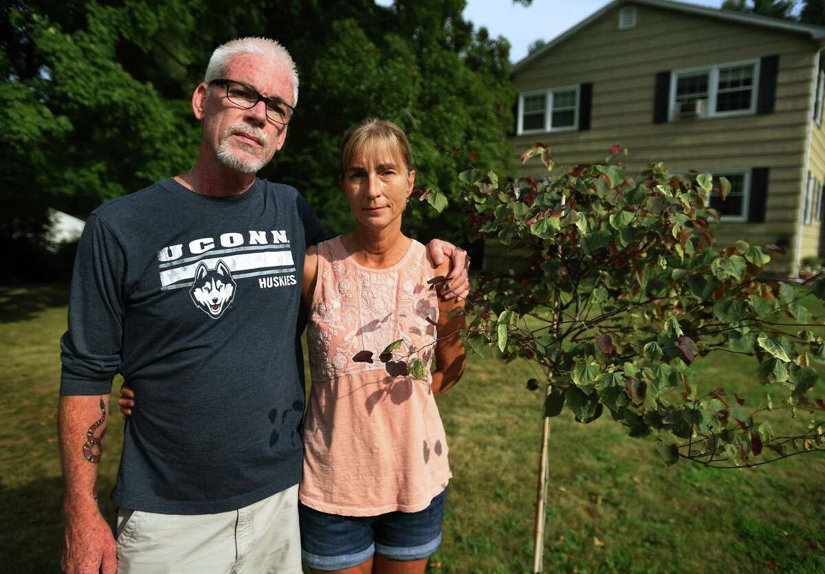 Wally and Niki Beddoe stand beside a tree planted in honor of their son outside their home in Trumbull, Conn. on Tuesday, August 11, 2020. The Beddoe's recently lost their 25-year-old son, Jake, from accidental fentanyl ingestion.