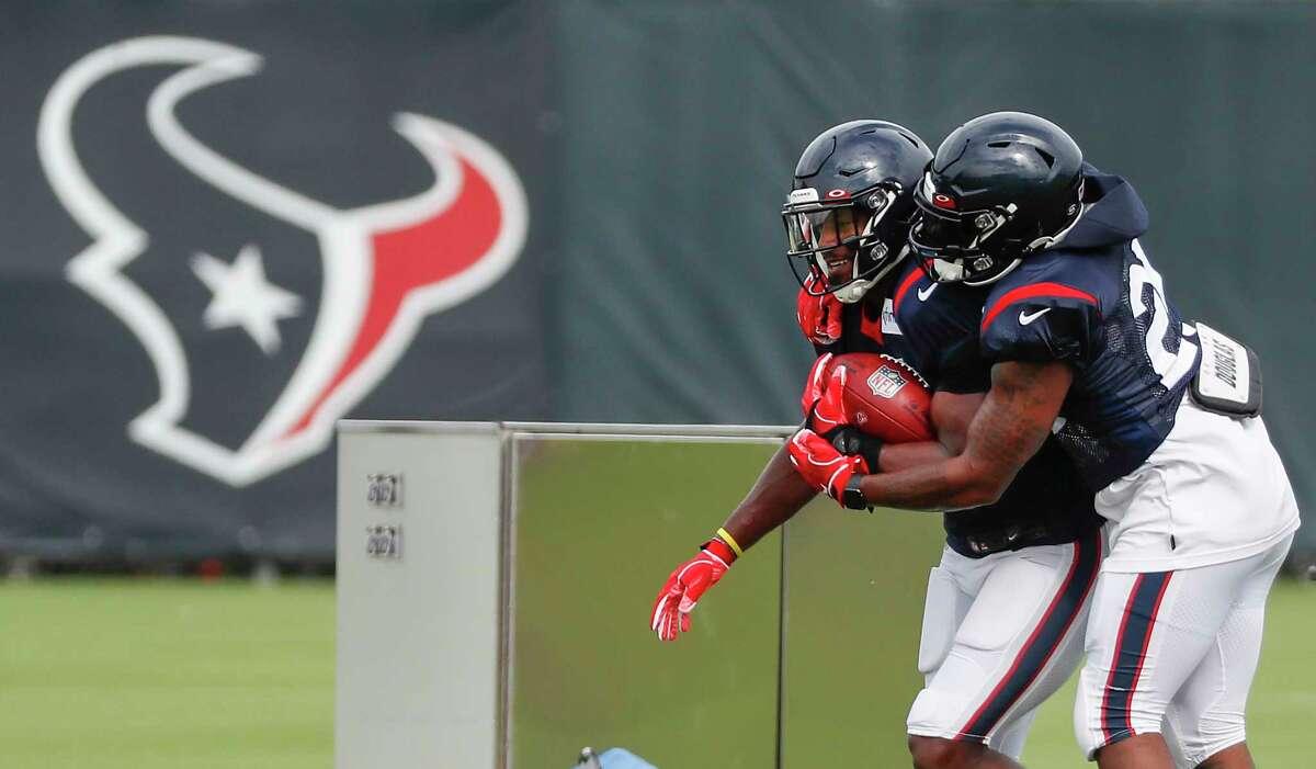 Houston Texans running backs David Johnson, left, and Duke Johnson (25) run a ball control drill during an NFL training camp football practice Monday, Aug. 17, 2020, at The Houston Methodist Training Center in Houston.