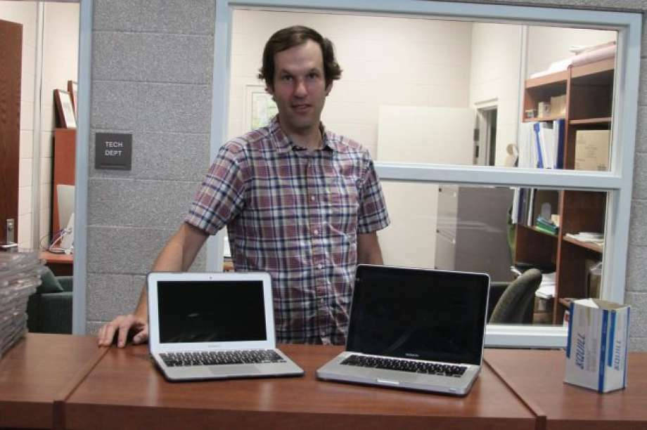 Manistee Area Public Schools technology director Ken Blakey-Shell shows off one of the 11-inch screen laptops next to the older 13-inch ones in this file photo. Blakey-Shell said that the district has been successful in getting devices back from students and repair rates have decreased. (File photo) Photo: News Advocate File Photo
