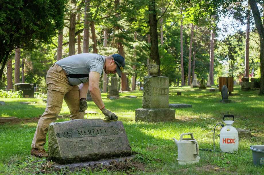 "Justin Frost of Midland cleans the headstone of Gilbert and Glatise Merritt as part of his new business, called ""Past Preservation,"" Wednesday, Aug. 12 at Midland Municipal Cemetery. (Katy Kildee/kkildee@mdn.net)"