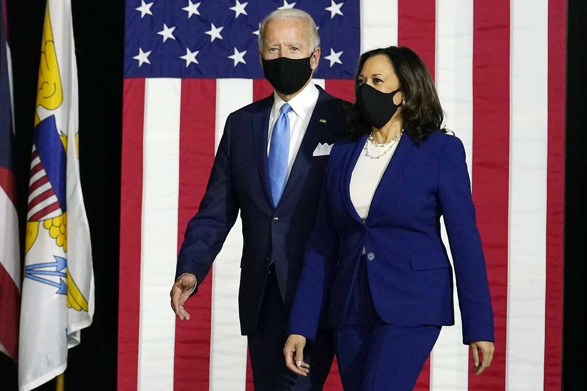 FILE - In this Aug. 12, 2020, file photo Democratic presidential candidate former Vice President Joe Biden and his running mate Sen. Kamala Harris, D-Calif., arrive to speak at a news conference at Alexis Dupont High School in Wilmington, Del. As Democrats gather virtually this week to nominate Joe Biden for the presidency, party leaders and activists across the political spectrum agree on one unifying force: their desire to defeat President Donald Trump. (AP Photo/Carolyn Kaster)