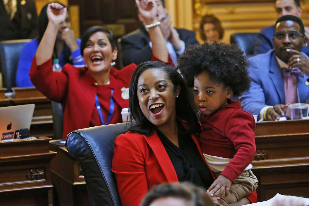 Virginia Delegate Jennifer Carroll Foy holds her son, Alex Foy, as she and Delegate Hala Ayala celebrate the passage of the Equal Rights Amendment in the House chambers at the Capitol in Richmond in January. Virginia was the 38th state to ratify the amendment.