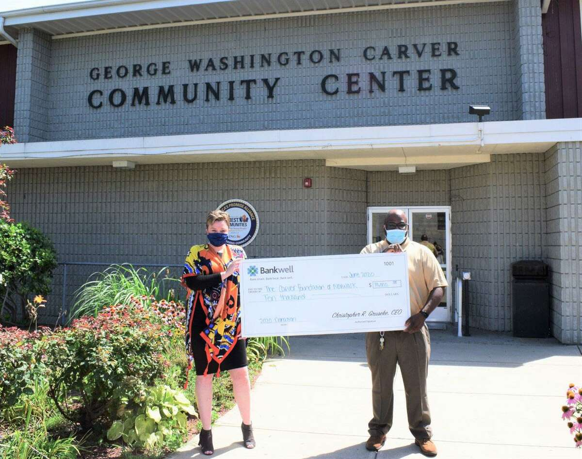 From left, Lucy French, vice president and marketing manager at Bankwell presents a $10,000 check to Brian Allert, chief program officer at the Carver Foundation of Norwalk for the benefit of students in Carver's after-school programs.
