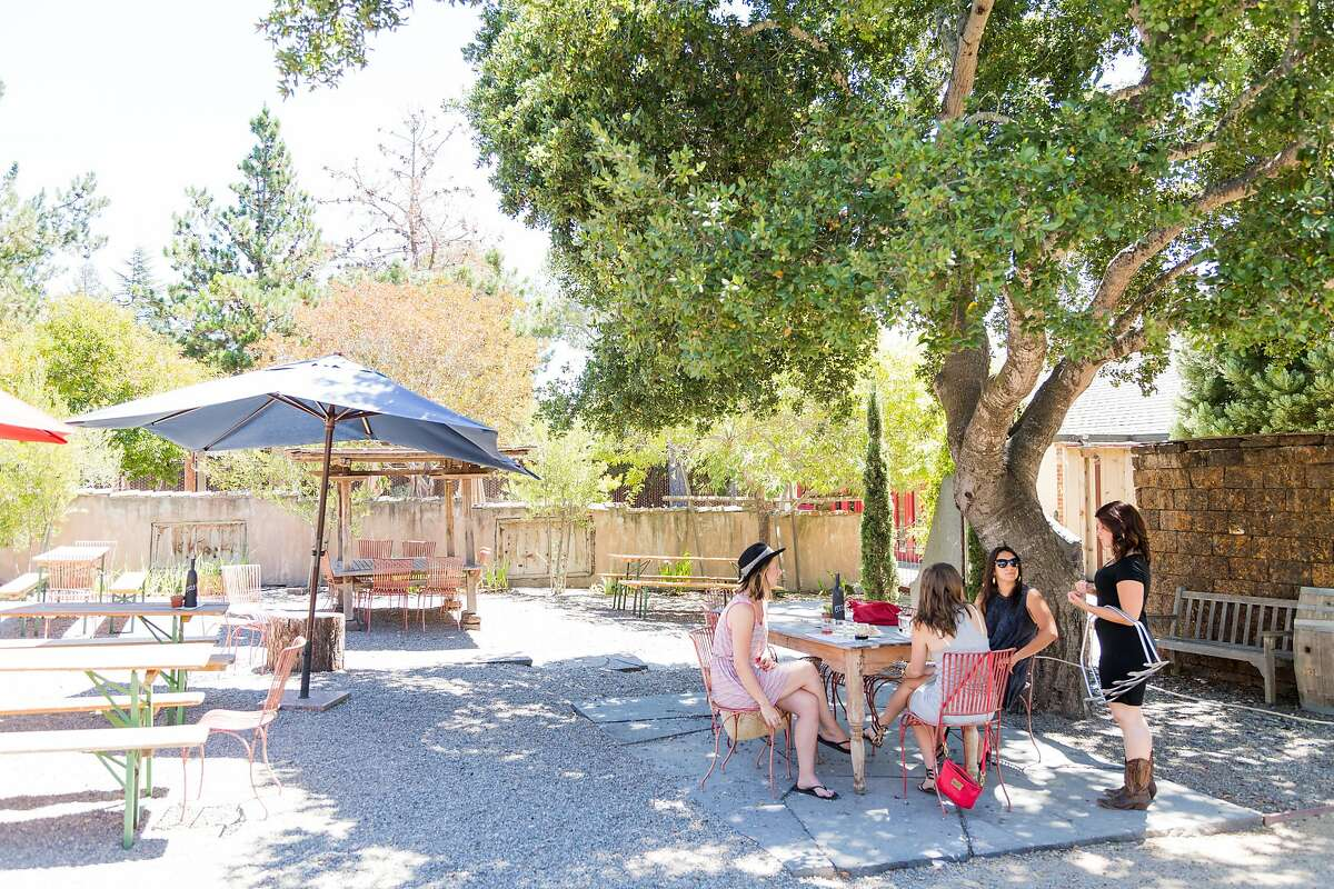 Guests sip wines under the shade of trees outside at Cowgirl Winery in Carmel Valley, Calif., Friday, August 14, 2015.