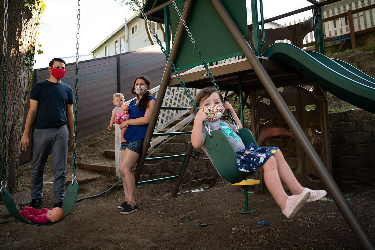 Alex Sobieski (left), 10-month-old Desiree and Grace Sobieskiwatch as Josie, 2, swings on a play structure in their backyard in Pacifica.