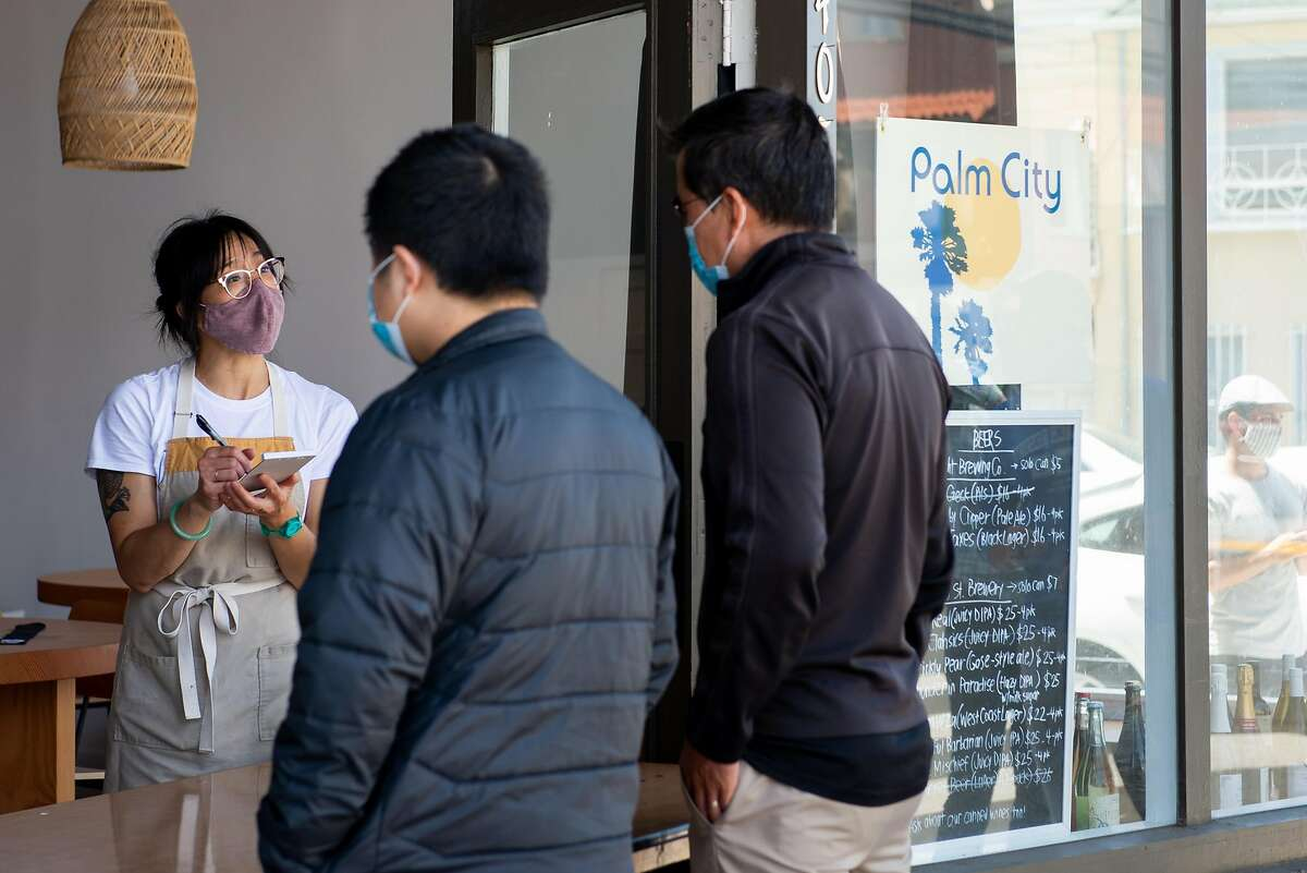 Customers line up outside of Palm City, a restaurant that pivoted their business strategy in the midst of the pandemic to churning out some of the best sandwiches in the city, while Monica Wong takes with hoagie orders on August 7, 2020 in San Francisco, Calif.